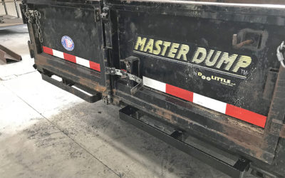 The loading ramp attachment brackets were bent and unusable on this dump trailer. This photo shows the nasty old one on the left, and on the right, the new one we fabricated and installed (yes, we replaced the other one, too!).